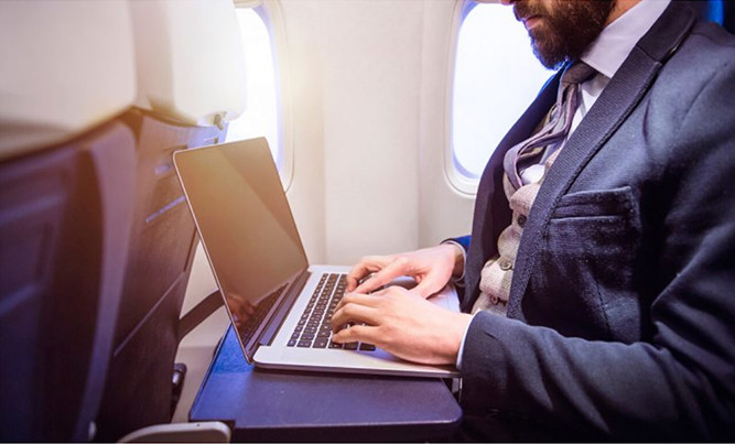Man typing on laptop on a plane